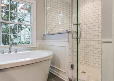 freestanding white tub next to subway tile shower