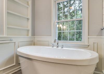 freestanding white soaker tub next to window