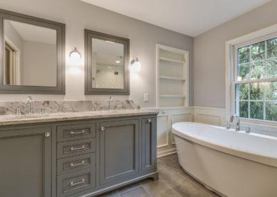 double sink vanity next to freestanding bath tub