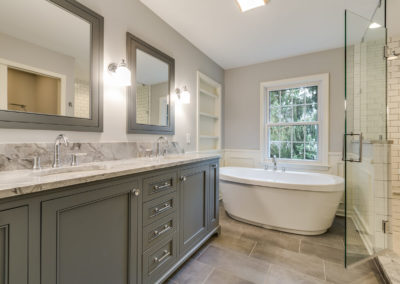 gray bathroom with freestanding tub and glass door shower