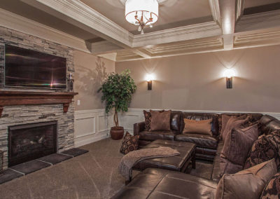 living room with stone fireplace and leather sectional