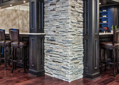 custom basement bar with wraparound seating and stone wall
