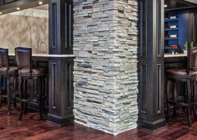 custom basement bar with wraparound seating and stone wall
