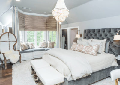 bedroom with gray velvet headboard and chandelier