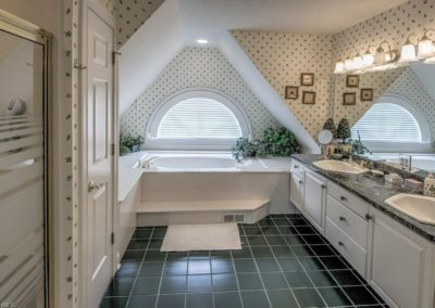 dated master bathroom with black tile floor and wallpaper before remodel