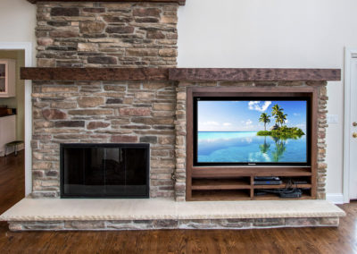 stone fireplace next to built in TV console