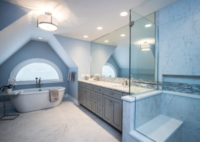 light blue master bathroom with freestanding tub, double vanity and tile shower