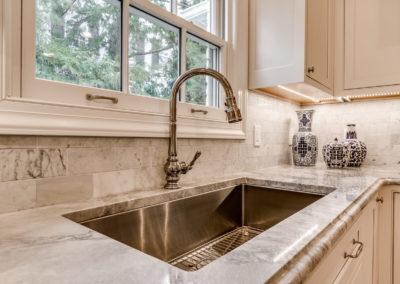 undermount stainless steel sink in modern white kitchen