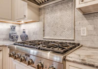 marble tile backsplash behind gas cooking range