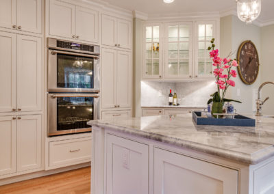 white kitchen with double stainless steel ovens