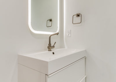white bathroom vanity with lighted mirror