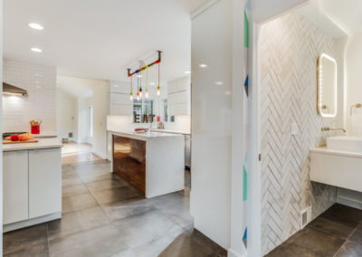 modern kitchen and half bathroom with tile wall
