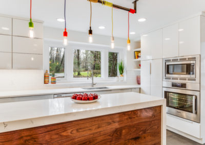white modern kitchen with multi colored pendant cord light fixture