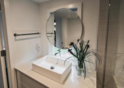 bathroom vanity with raised sink and circular mirror