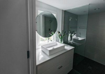 raised sink vanity with circular mirror