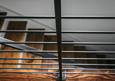 black railing overlooking wood stairs