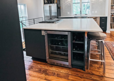 large kitchen island with built in wine fridge and rack