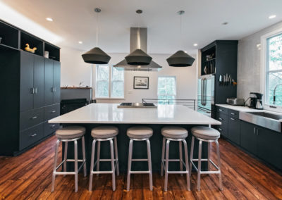modern kitchen with black cabinets and pendant lighting