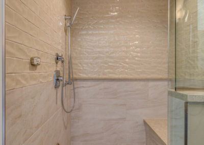 beige tile shower with bench