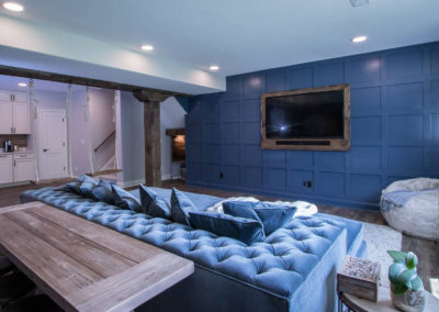basement entertainment area with blue sofa and wall