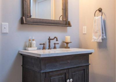 half bathroom with rustic single sink vanity