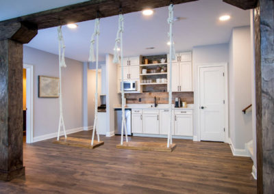 renovated basement with half kitchen and custom indoor swings