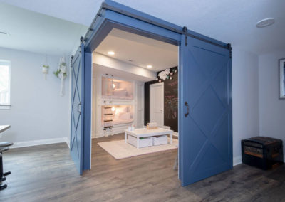 sliding blue barn doors to basement bunk room