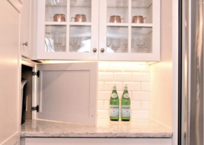 white kitchen cabinet door open to hidden appliance storage