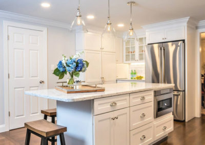 classic white kitchen island with storage and microwave