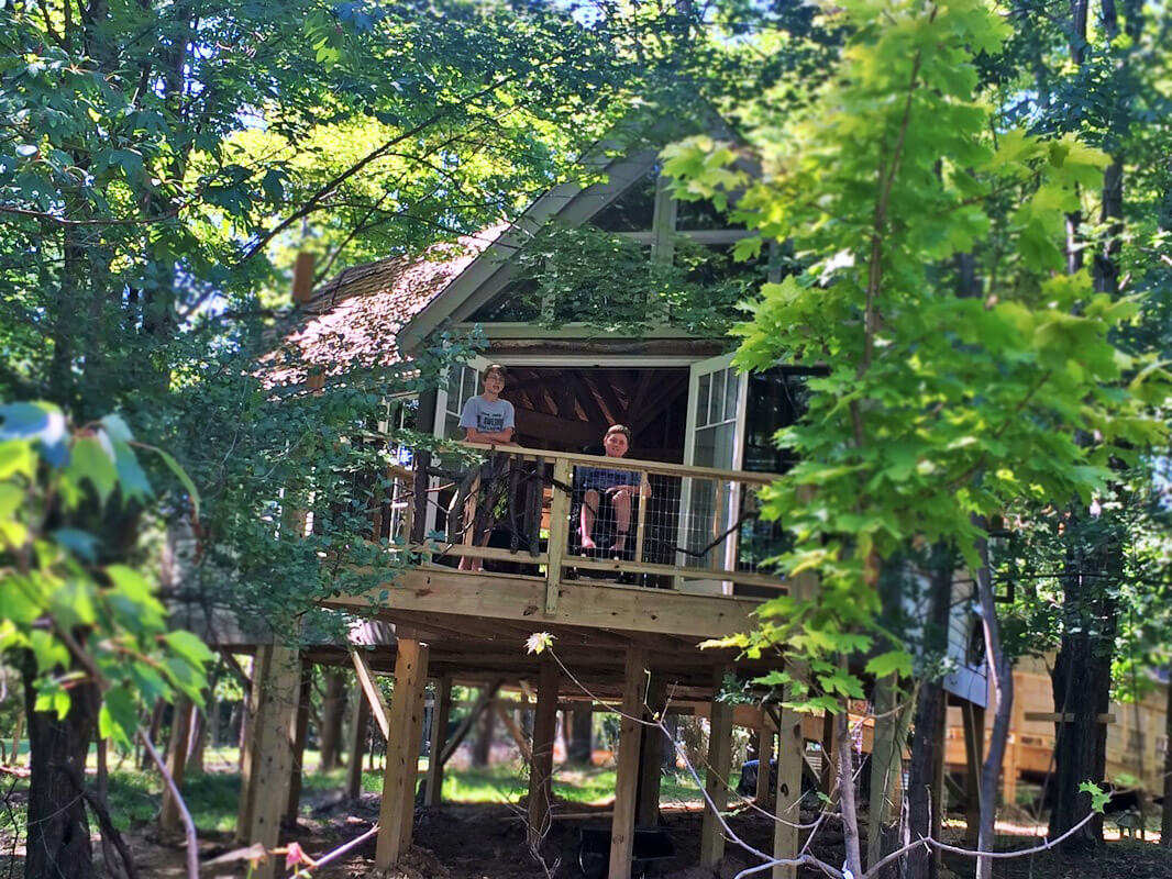 owen and a friend on the porch of Owen's treehouse