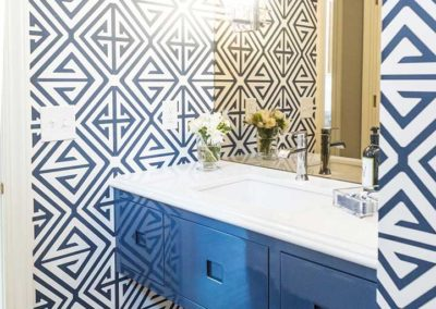 bathroom with blue wall mounted vanity and geometric blue wallpaper