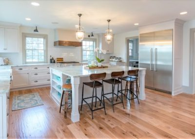 farmhouse kitchen with hickory hardwood floor and white cabinetry