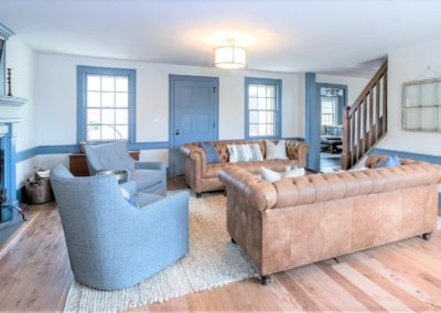 sofas and arm chairs on area rug in farmhouse living room