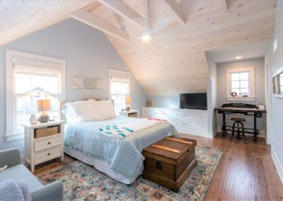 bedroom with vaulted wood ceiling and blue accent colors