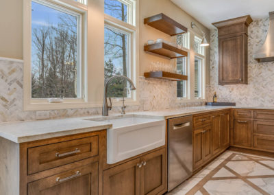 remodeled kitchen with wood cabinetry and floating shelves
