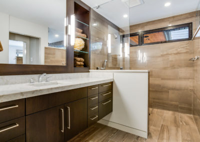 master bathroom with wall mounted vanity and tile shower