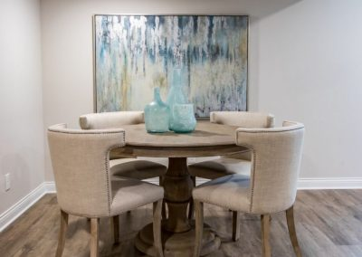 circular wood dining table with upholstered chairs