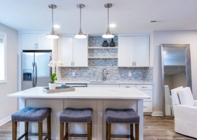 white kitchen island with three stools