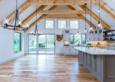 kitchen open to dining room with exposed beam vaulted ceiling