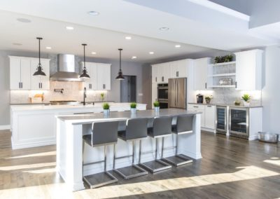 spacious white kitchen remodel with work island and seating island