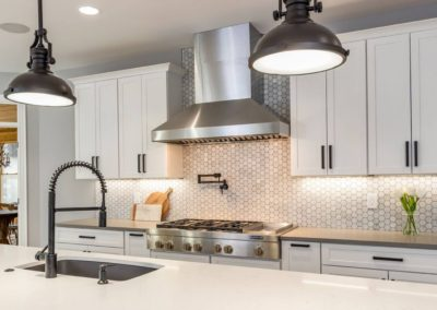 white kitchen with stainless steel gas range and range hood and tile backsplash