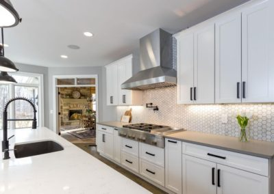 white kitchen with stainless steel gas range and range hood
