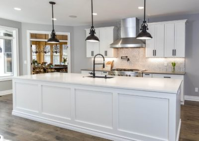 white kitchen island with black pendant lighting