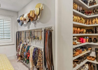 remodeled master closet with accessory racks and shoe shelving