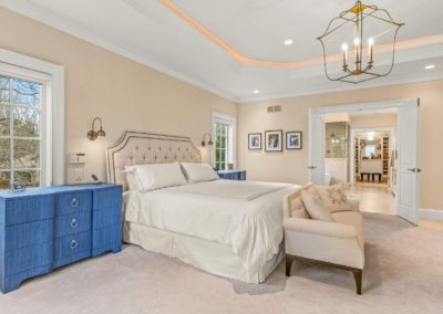 spacious master bedroom with blue nightstands and gold chandelier lighting