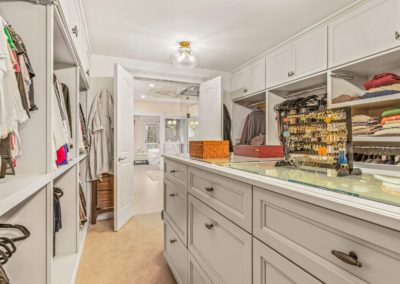 master closet with white cabinets and built in shelving
