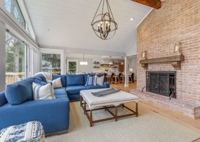living room renovation with blue sectional and brick fireplace