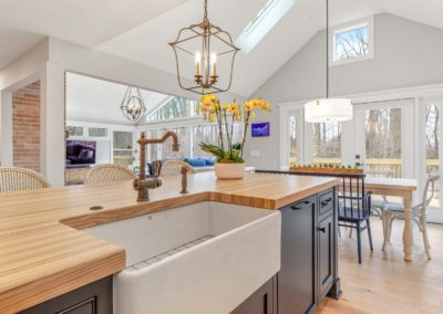 remodeled kitchen with white farmhouse sink and butcher block island countertop