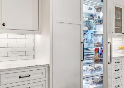 fridge with white cabinet panel doors in farmhouse kitchen