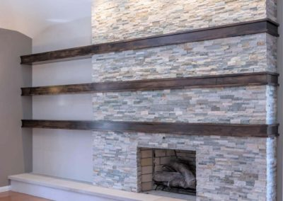 stone fireplace with brown shelving